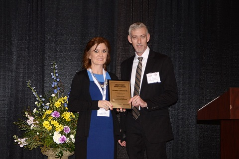 Woman presents man with award